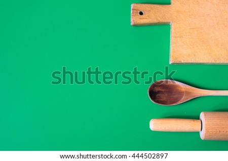 Vintage wooden utensils set. Wooden spoon, rolling pin and cutting tabletop on green background.  - stock photo