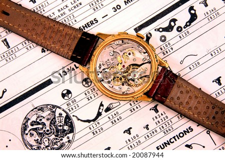 Vintage wrist watch, movement revealed, on vintage watch parts list. - stock photo