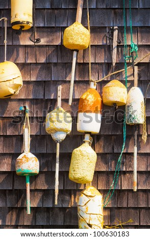 Vintage yellow and orange lobster and fishing floats or buoys hanging on a wood shingled wall. - stock photo