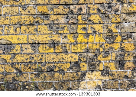 vintage yellow brick wall pattern background with bullet holes from WW2. - stock photo