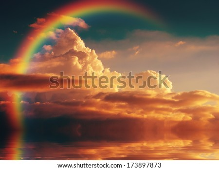 Vintage yellow clouds with rainbow, reflected in a river - stock photo