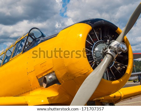 Vintage Yellow Propeller Aircraft Parked at an Airport - stock photo
