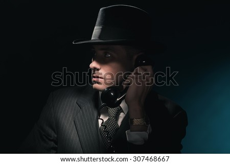 Vintage young detective on the phone with hat in suit and tie. Dark blue background. - stock photo