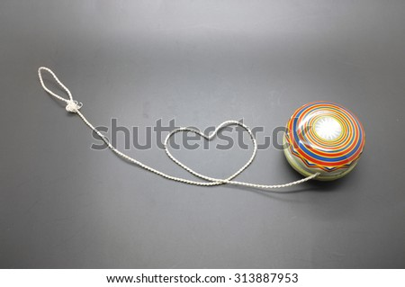 Vintage yoyo with twine rolling in heart shape - stock photo