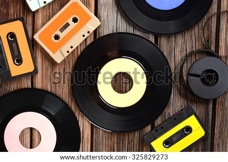 vinyl disc and cassette tapes on the wooden table - stock photo