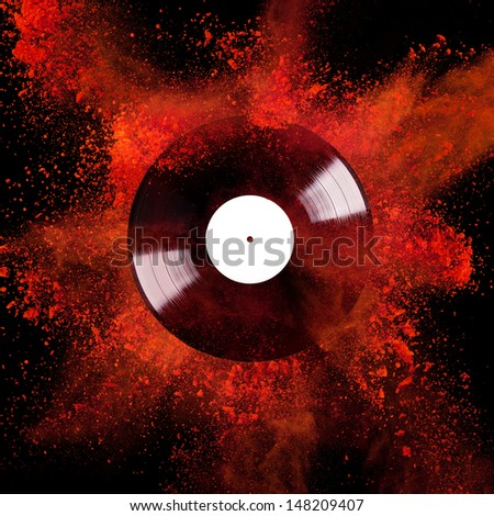 Vinyl disc with colored powder over black background - stock photo