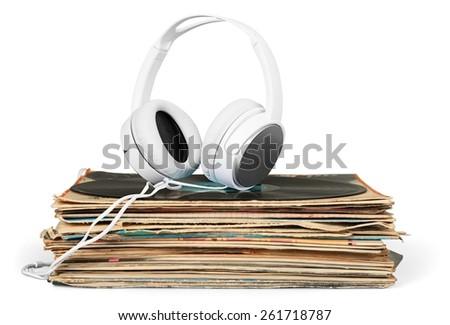 Vinyl. Golden headphones lying on the stack of vinyle records. - stock photo