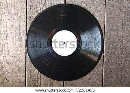 vinyl record on old wooden background - stock photo