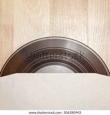 Vinyl record with cover on wooden table background - stock photo