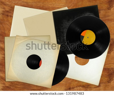 Vinyl records and covers on table - stock photo