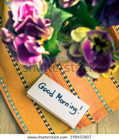 Viola flowers in a vase, old-styled clock and Good morning note on the table - stock photo