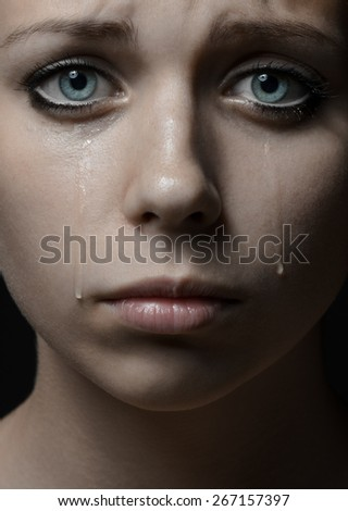 Violence and abuse of girls theme: portrait of a beautiful young girl with tears in her eyes, a beautiful sad girl in the studio - stock photo