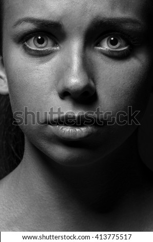 Violence and abuse of girls theme: portrait of a beautiful young girl with tears in her eyes, a beautiful sad girl in the studio shot black and white portrait - stock photo