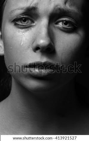 Violence and abuse of girls theme: portrait of a beautiful young girl with tears in her eyes, sad woman in the studio shot black and white photo - stock photo