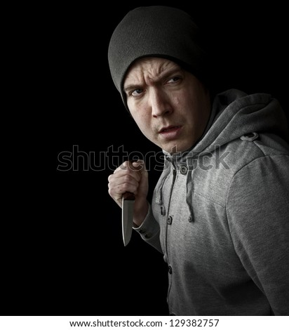 violent crime, man with knife on black background with copy space - stock photo