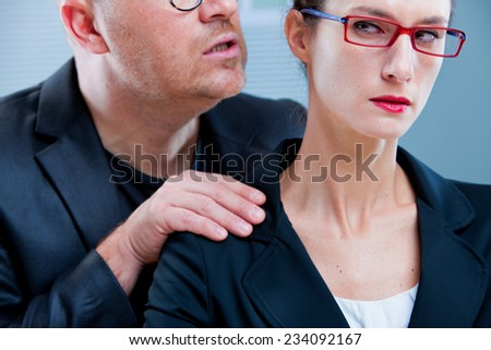 violent man menacing an office worker woman maybe his colleague or subordinate - stock photo
