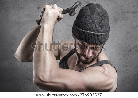 Violent man using a spanner or wrench as a weapon beating down with blows on something below him, close up head and shoulders - stock photo