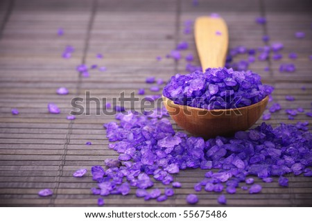 Violet bath salt in wooden spoon on brown mat. - stock photo