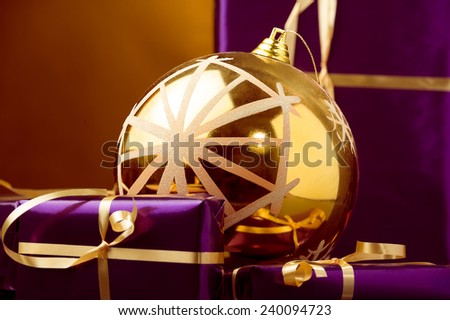 violet Christmas gift boxes and Xmas gold ball decoration - stock photo