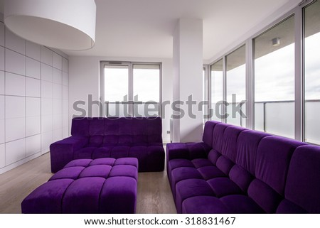 Violet quilted sofa in modern sitting room - stock photo