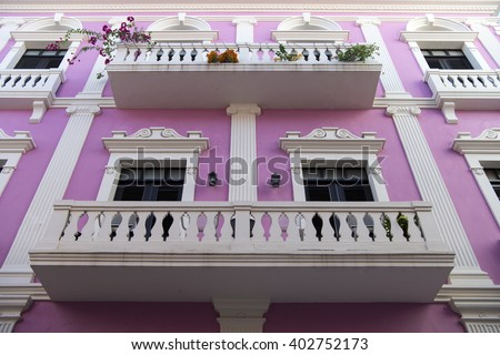 Violet residential building house with white beautiful balcony fence and doors with windows in San Juan, Puerto Rico - stock photo