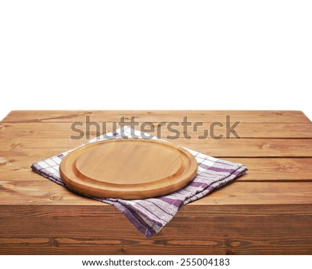 Violet tablecloth or towel over the surface of a brown wooden table with a round wooden tray on top of it, composition isolated over the white background - stock photo