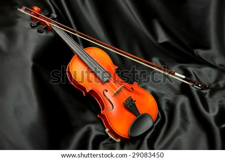 Violin and bow on black silk, music background - stock photo