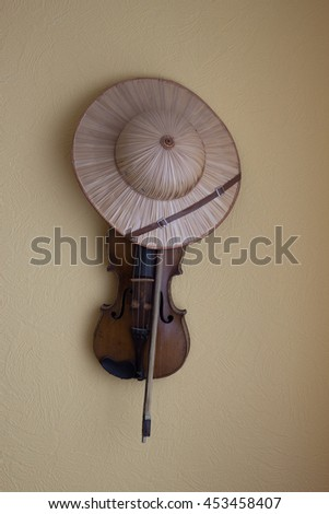 violin and hat hanging on wall. Music voyage - stock photo