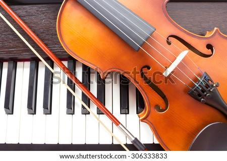 Violin and piano keyboard. Music background. Top view. - stock photo