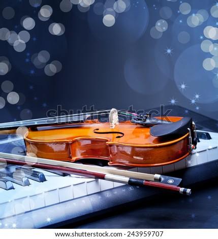 Violin and piano keys on black - stock photo