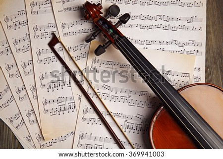 Violin neck on music papers background - stock photo