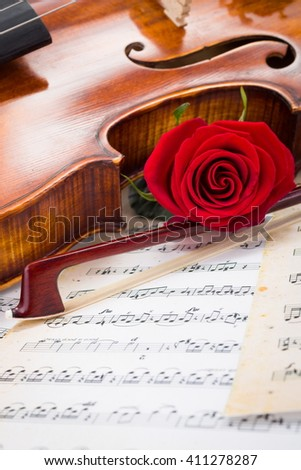 Violin, red rose and bow on musical score - stock photo