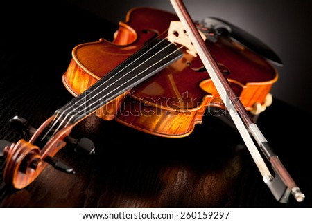 Violin with bow in ftont of a dark background - stock photo