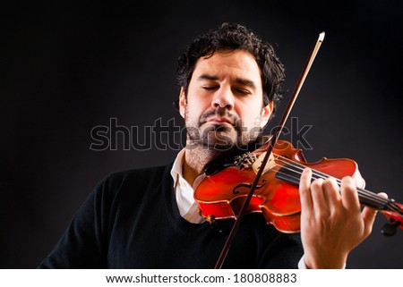 Violinist playing in black background. - stock photo