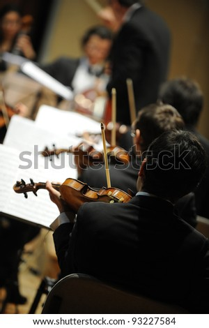 violinists during a classical concert music, music conductor on background - stock photo