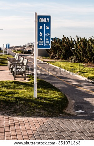 Virginia Beach oceanfront boardwalk bike path with benches. - stock photo