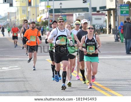 VIRGINIA BEACH, VIRGINIA - MARCH 16: Runners compete in the Yuengling Shamrock Marathon in Virginia Beach, Virginia March 16, 2014 - stock photo