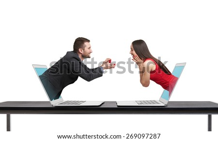 virtual couple got out of the computers. amazed happy woman looking at gift and happy man looking at her. isolated on white background - stock photo