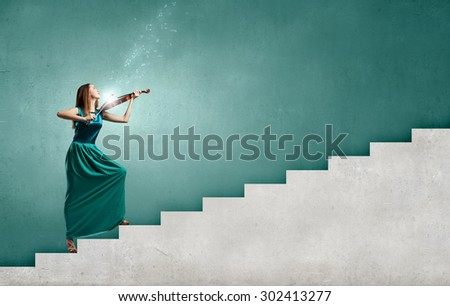 Virtuoso violin female player in green dress - stock photo