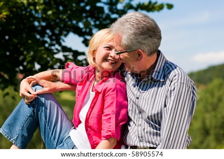 Visibly happy mature or senior couple outdoors arm in arm deeply in love, she is showing him something - stock photo