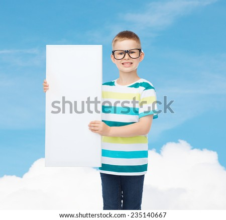 vision, health, advertisement and childhood concept - smiling little boy in eyeglasses with blank board over blue cloudy sky background - stock photo
