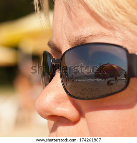 Vision of summer vacation - beach scene reflected in woman sunglasses - stock photo