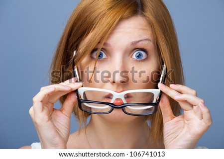 Vision without glasses. Amazed young woman with blue eyes holding two pairs of glasses in their hands - stock photo