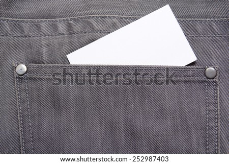 visiting card in back pocket of old grey jeans - stock photo