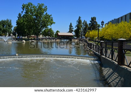Visitors to Bakersfield, California's Central Park benefit from the use of agricultural irrigation water as it passes through. - stock photo