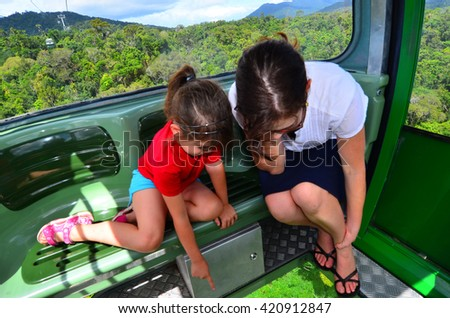 Visitors travel on Cableway above the Barron Gorge National Park a World Heritage in the Wet Tropics of Queensland, Australia. - stock photo