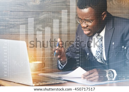 Visual effects. African American office worker wearing formal wear and glasses, gesturing and yelling in annoyance irritated with a computer problem while working on laptop sitting against wooden wall - stock photo