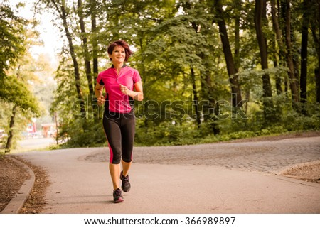 Vital senior woman jogging in park on summer evening - stock photo