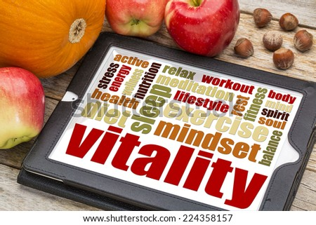 vitality or vital energy word cloud on a  digital tablet with apples, pumpkin and hazelnuts - stock photo