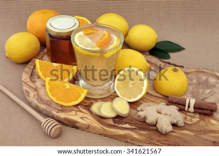 Vitamin c health remedy relief drink for cold and flu, with lemon and orange fruit, ginger and cinnamon spice and honey on an olive wood board. - stock photo